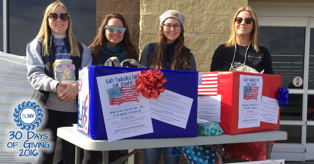 Female students at Fredonia stand behind table collecting care package gifts for troops.