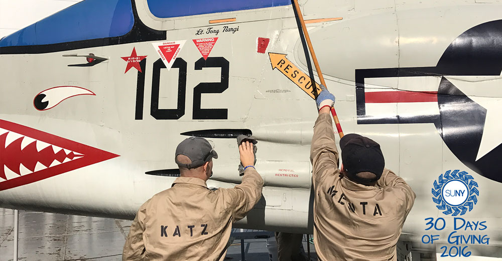 Maritime College cadets clean the side of a fighter plane.