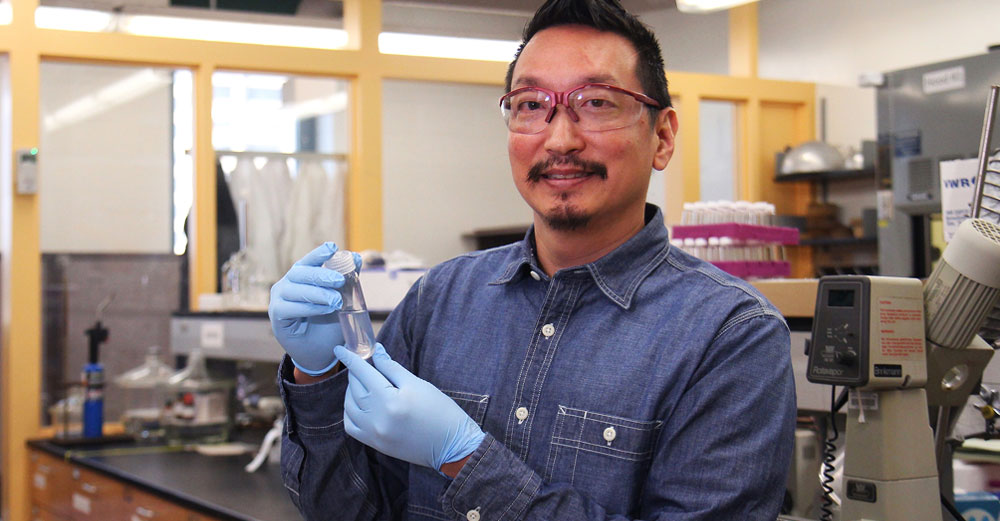 ESF professor Chris Nomura holds test tube with rubber gloves on in science lab.