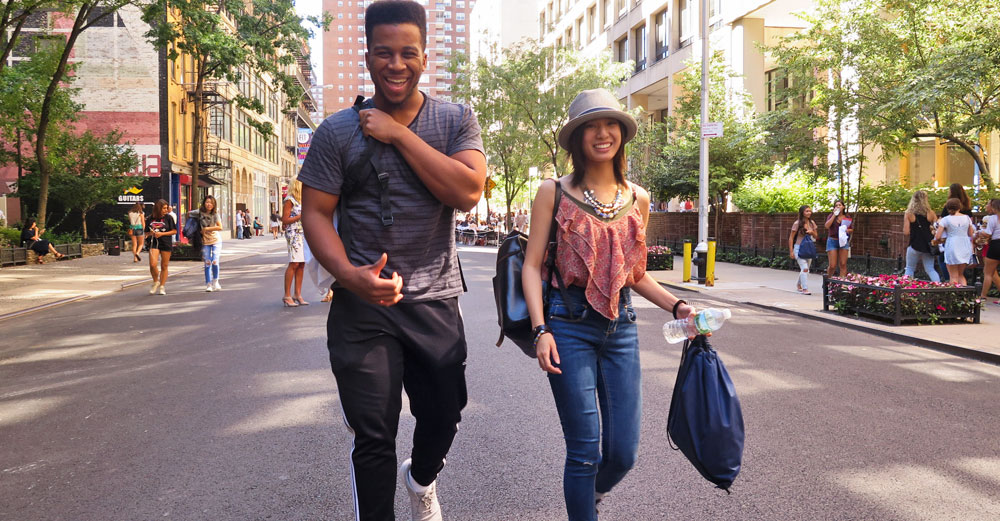 FIT students walking down NYC street with bags in hand.