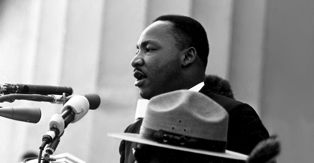 Martin Luther King Jr speaks at a microphone.