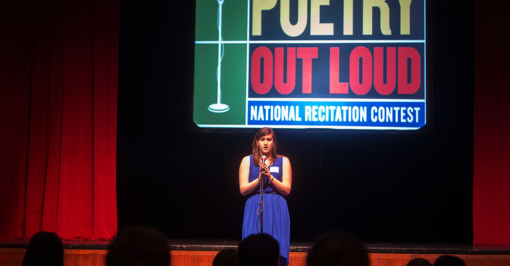 A student stands on stage at a Poetry Out Loud competition at Binghamton University
