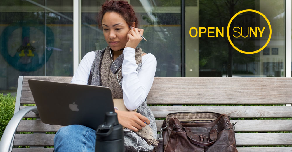 Girl outside on bench working on laptop with Open SUNY logo