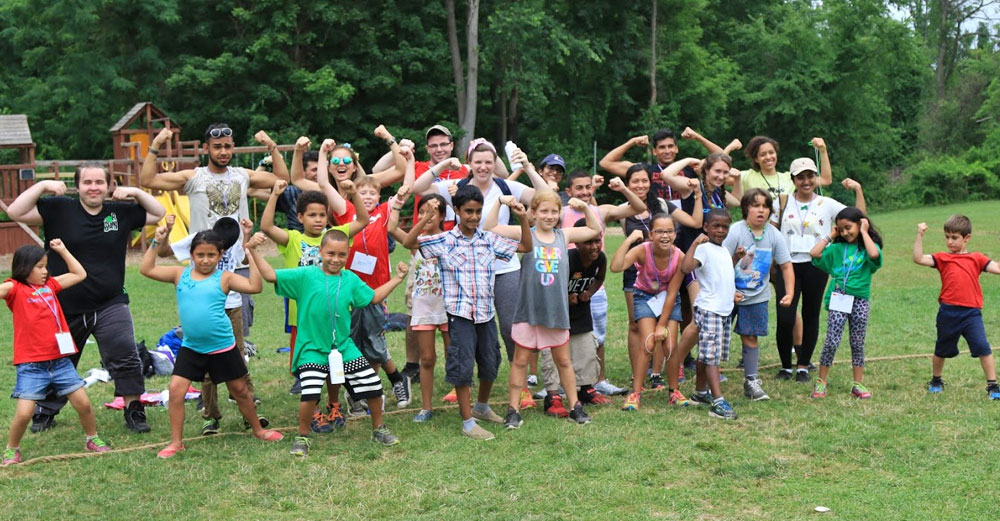 Stony Brook students with children at Camp Kesem pose for picture while flexing muscles outside at camp.