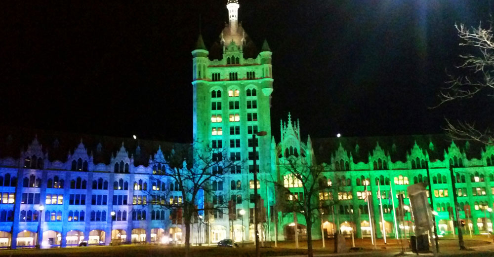 SUNY Plaza shines in blue and green lights at night.