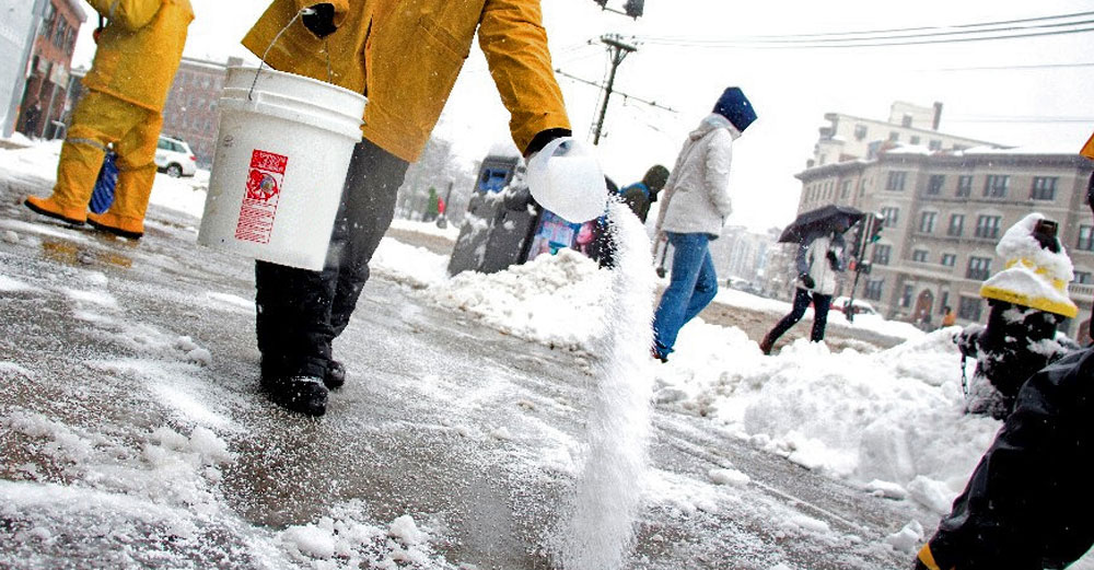 Man sprinkles salt on icey city sidewalk in winter.