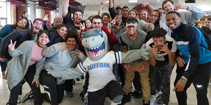 Finn Shark from SUNY Suffolk County Community College kneeling with a bunch of students raising their hands.