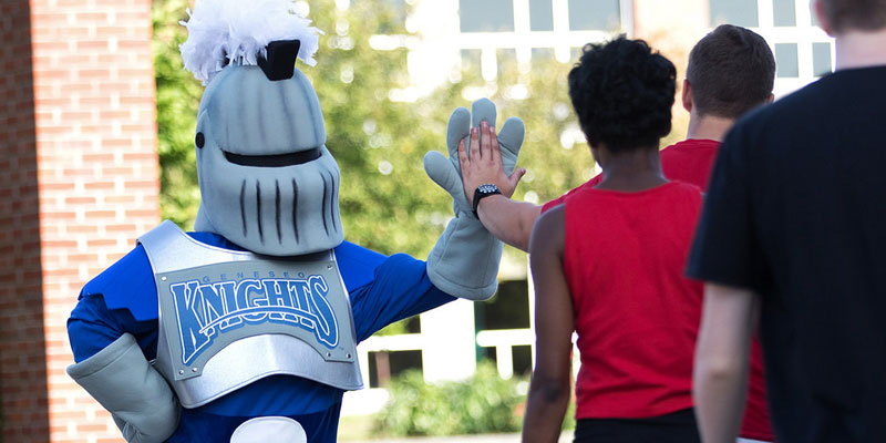 Geneseo Knight giving high fives to students outside.