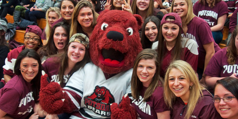 Potsdam mascot Max C bear sits in the stands with student fans.
