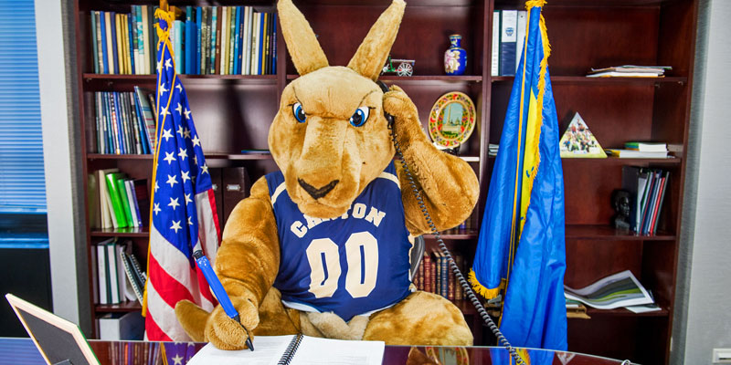 SUNY Canton mascot Roody Roo works at president's desk.