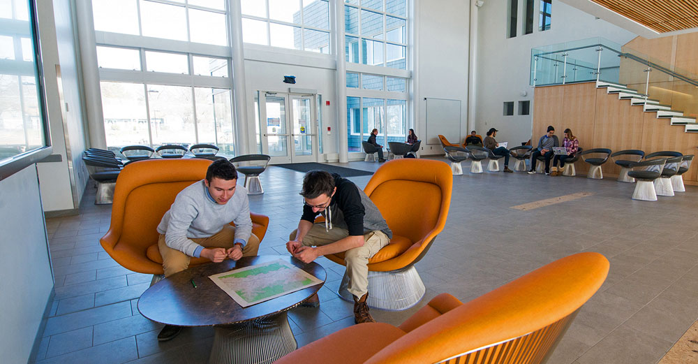 New SUNY New Paltz Science Hall lobby with students in yellow lounge chairs