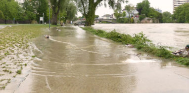 A river flooding over its banks onto road and sidewalk on the side.