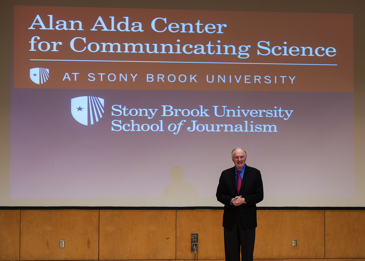 Alan Alda with SBU Alda Center logo