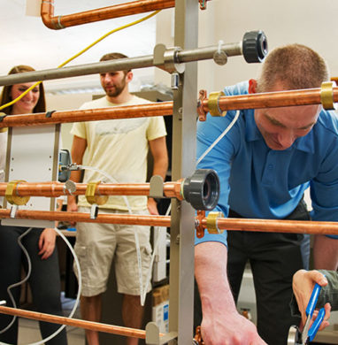 Enginnering students at SUNY New Paltz work around pipes.