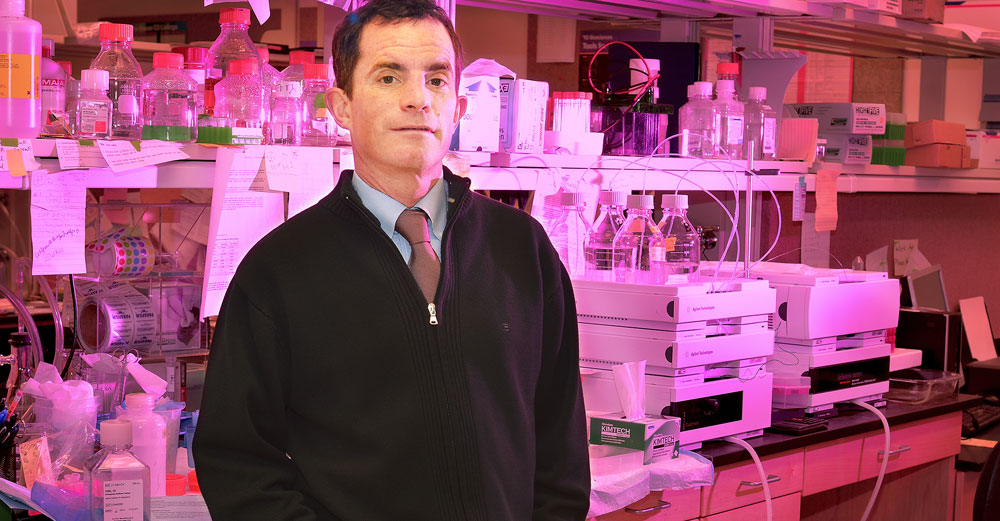 Upstate Medical University professor William Kerr stands in front of medical lab shelves.