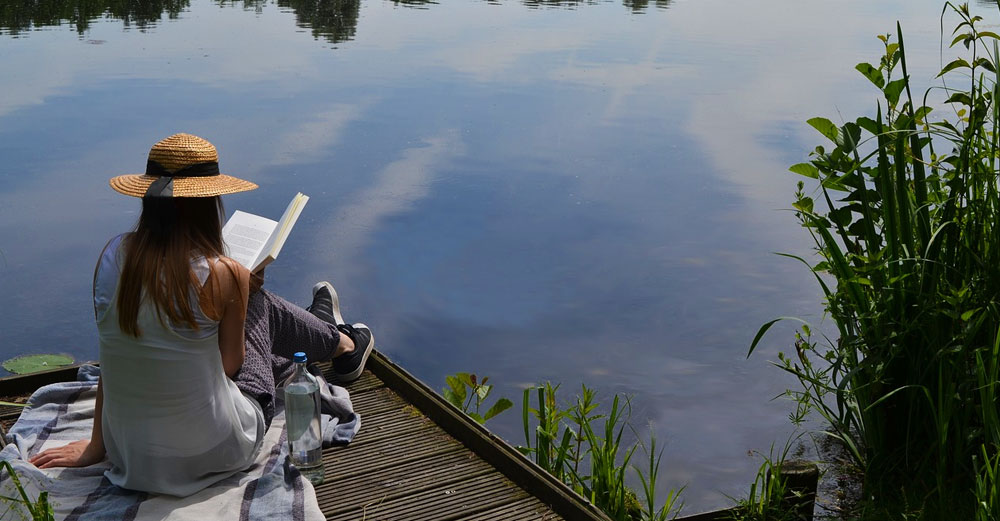 A girl reading a book on the dock overlooking a lake in the summer.