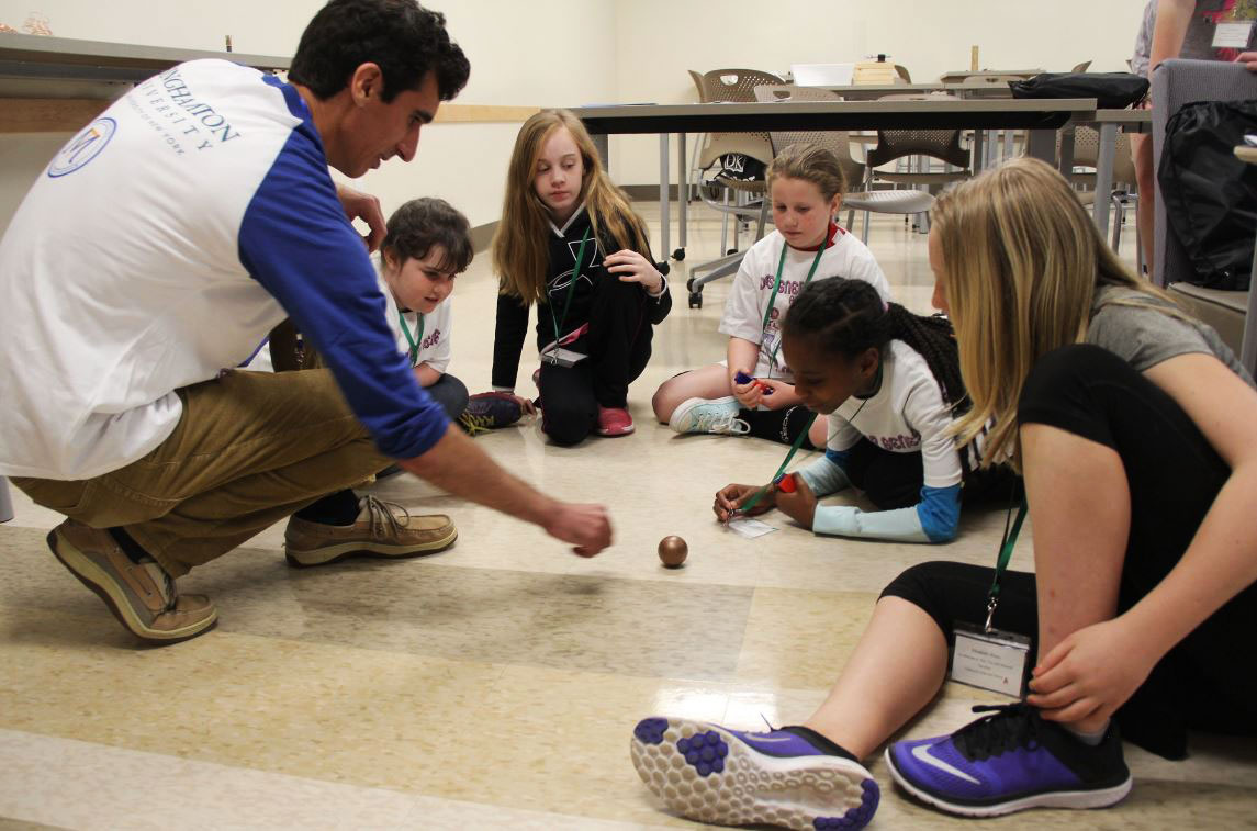 A male teacher spins a sphere on the floor in front of elementary school girls at the Girls in Stem event at Binghamton University.