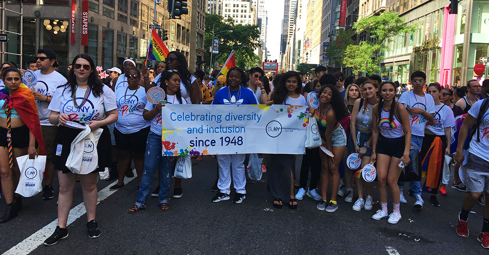 "SUNY students and staff pose with a banner that states ""celebrating diversity and inclusion since 1948"" at the 2017 NYC Pride Parade."