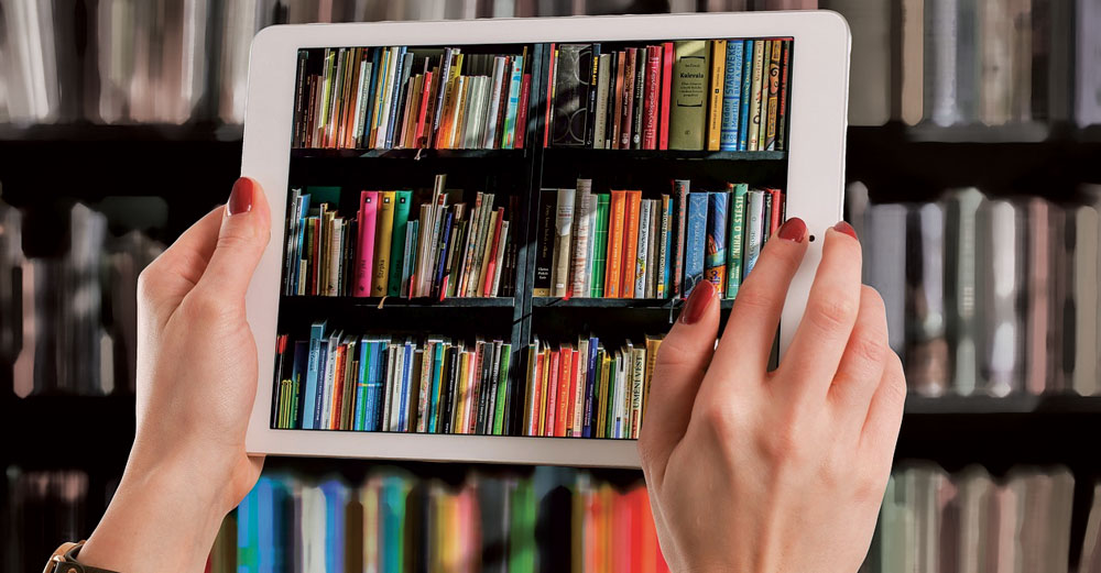Woman's hands holding tablet computer with picture of library book shelf in front of an actual library book shelf.