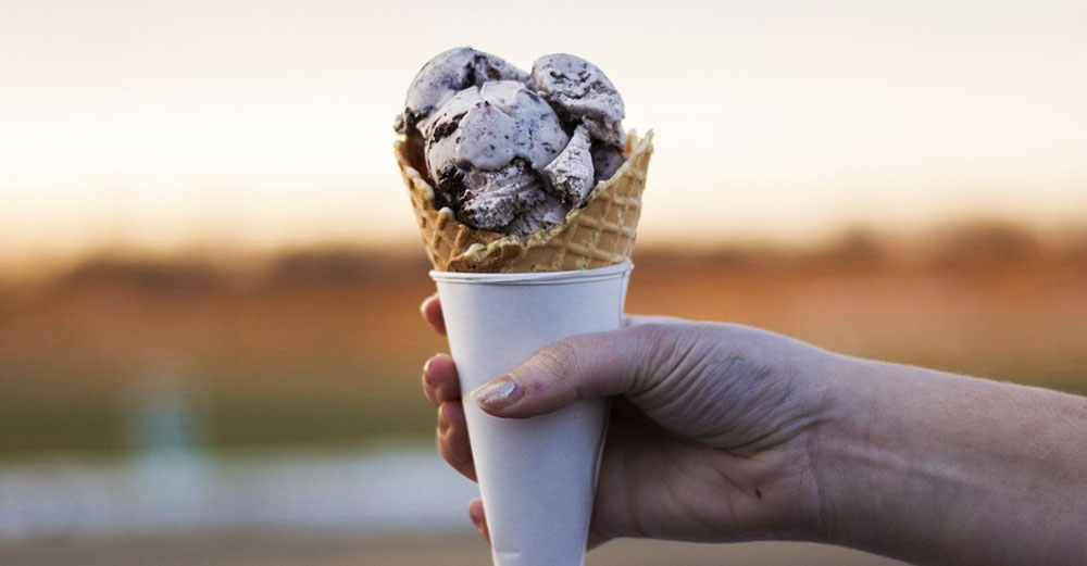 Outstretched hand holds ice cream in waffle cone.