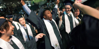 Binghamton University graduate pumps his arms in the air to celebrate in the crowd at commencement.