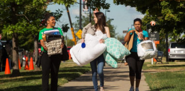 Female students at Buffalo State carry bags and boxes during move-in day.