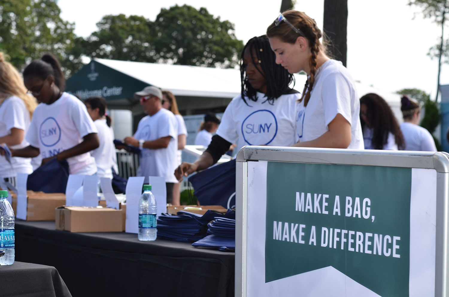 Student volunteers fill comfort bags at the Northern Trust Open in Old Westbury in front of a sign that says Make A Bag, Make A Difference.