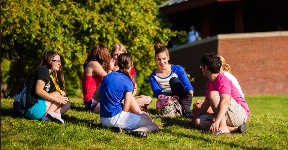 Students at SUNY Geneseo sit and talk on the lawn during a bright sunny day.