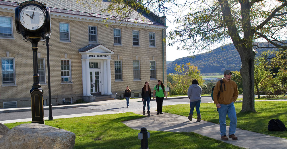 Students walk outside a building at SUNY Cobleskill