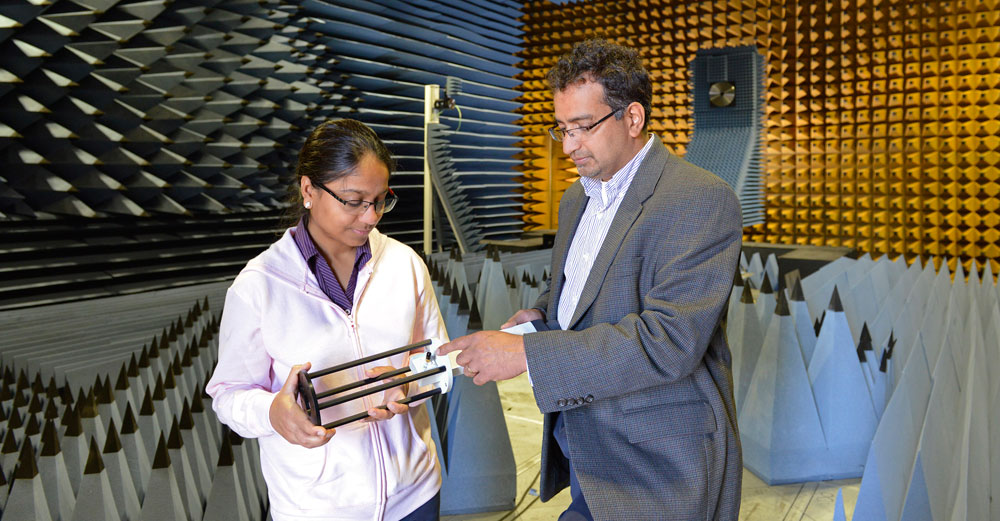 SUNY Oswego's Patanjali Parimi, director of the Advanced Wireless Systems Research Center, stands with female researcher.