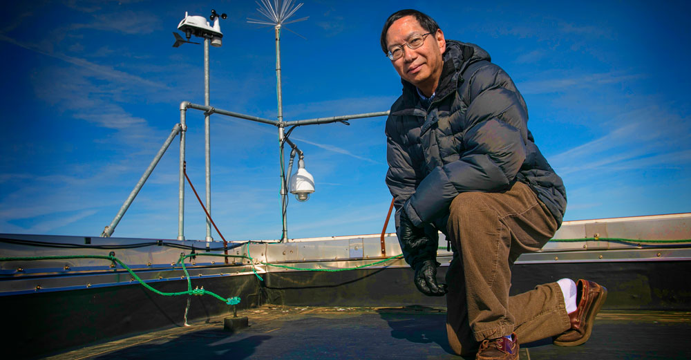 Dr Edmund Chang of Stony Brook University kneels on a rooftop in front of weather measuring tools.
