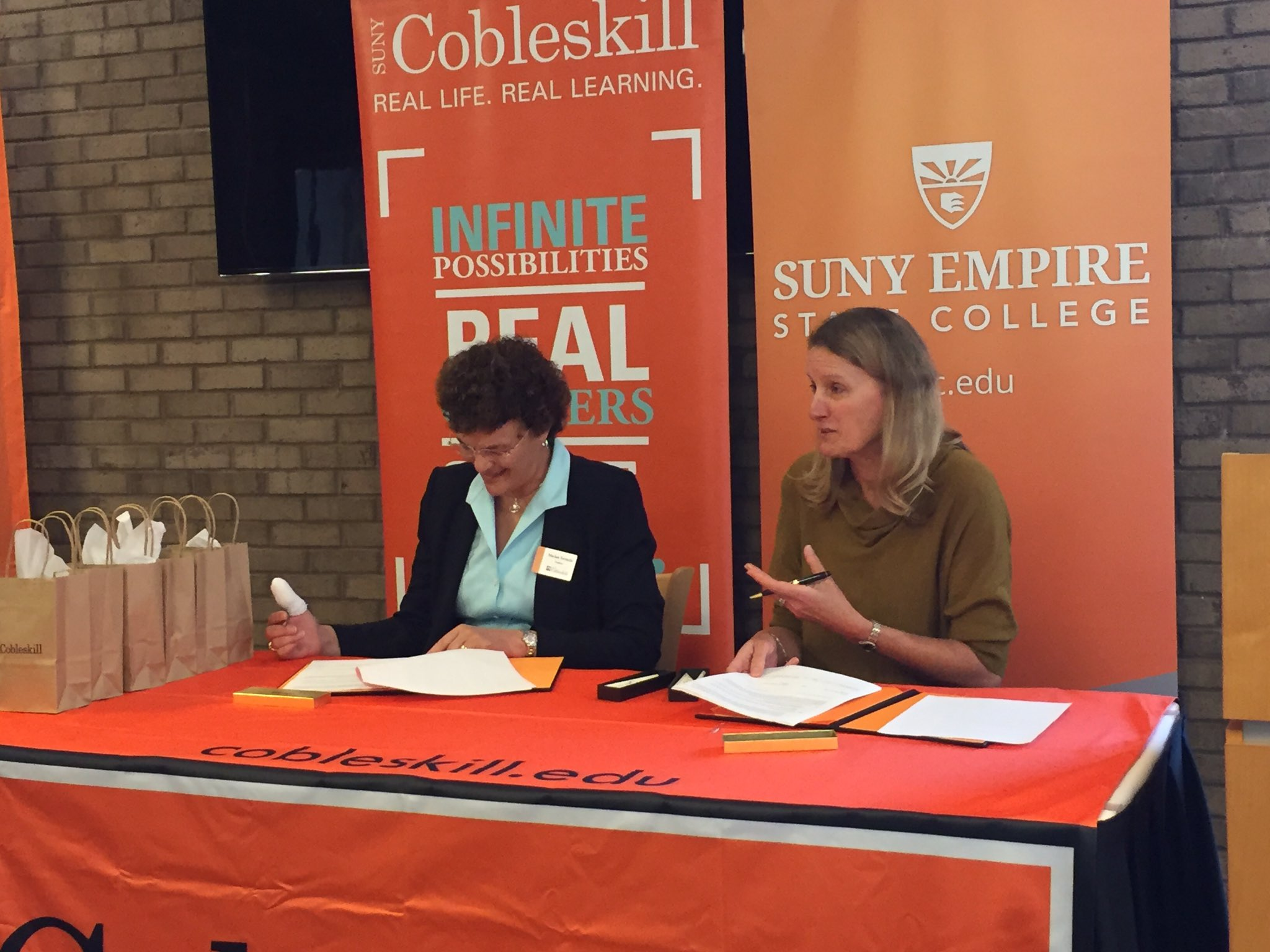 Cobleskill president Terenzio and Empire State College president Hancock sign a transfer agreement between the two schools.
