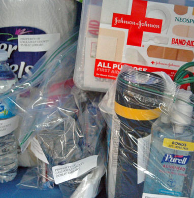 Emergency preparedness kit with first aid supply, paper towels, flash light, and more in a travel bag.