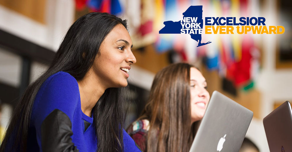 2 girls behind a laptop looking forward, with NY State Excelsior Ever Upward logo