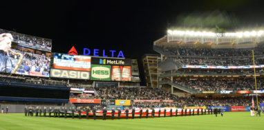 Maritime College cadets stand with a giant American Flag at Yankee Stadium before game 3 of the 2017 ALCS.
