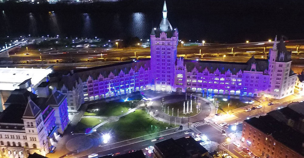 SUNY Plaza at night lit in purple lights.