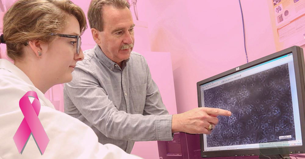 SUNY Poly professor Dr James Castracane points at computer screen with cancer cell diagaram as a female student looks on
