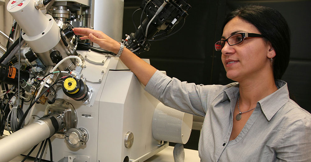 A female researcher stands in the lab near a scientific magnification tool.
