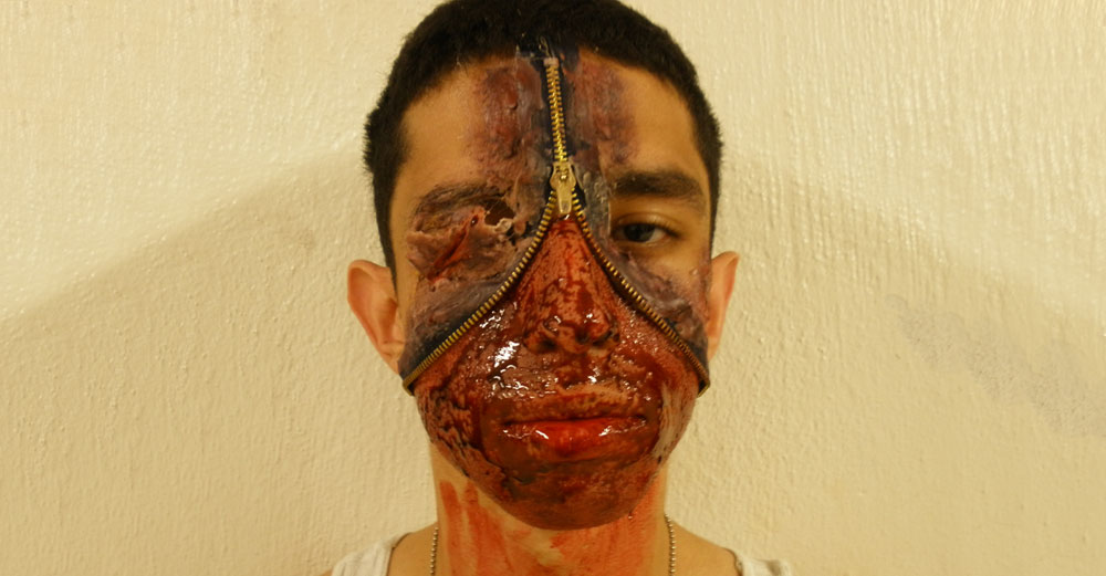 Student with bloody face makeup and a latex zipper opening into his face.