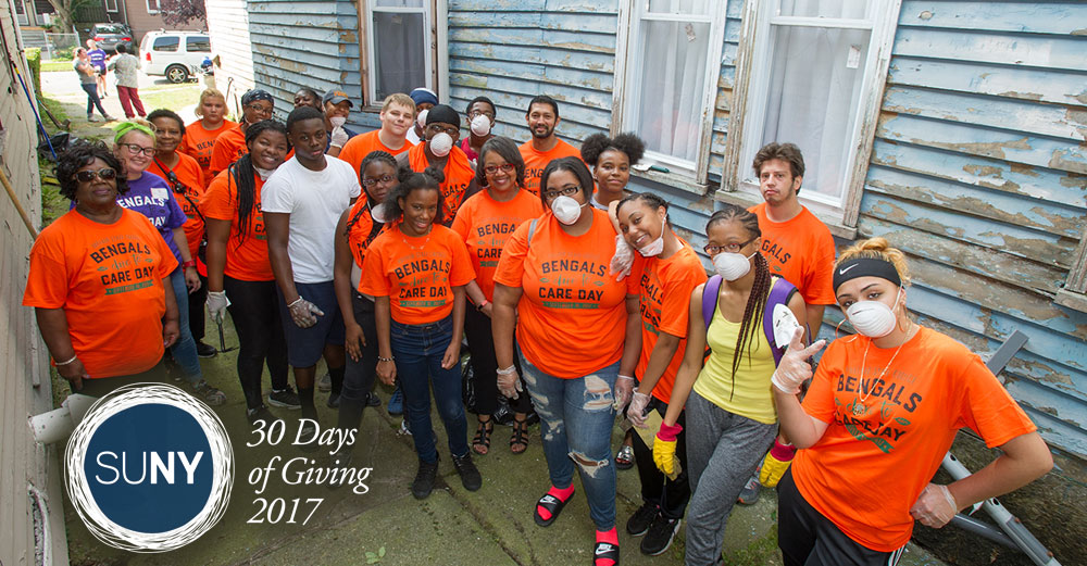 Large group of Buffalo State students pose for picture after cleaning up around a house in town.