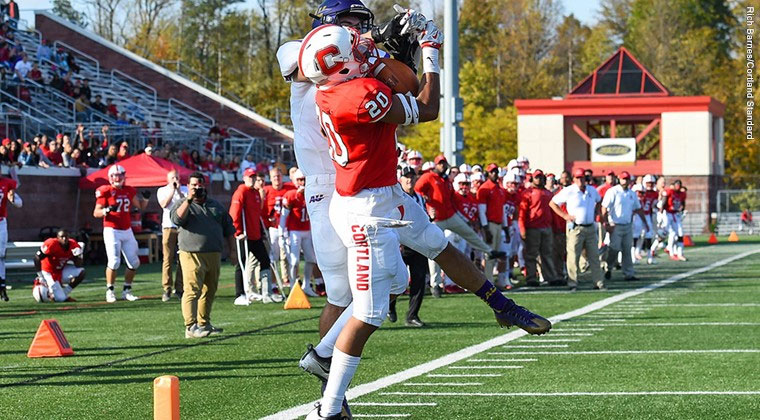 A Cortland football defensive back intercepts a pass against Alfred University