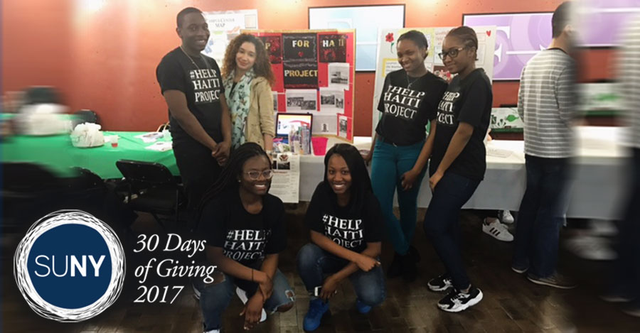 Students from WUNY Old Westbury pose in front of donations table wearing black tshirts with Help Haiti Project.