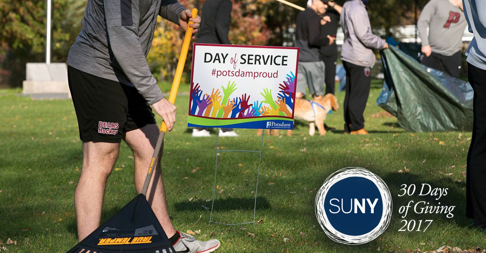A SUNY Potsdam student rakes leaves in front of a sign saying Day of Service #PotsdamProud.