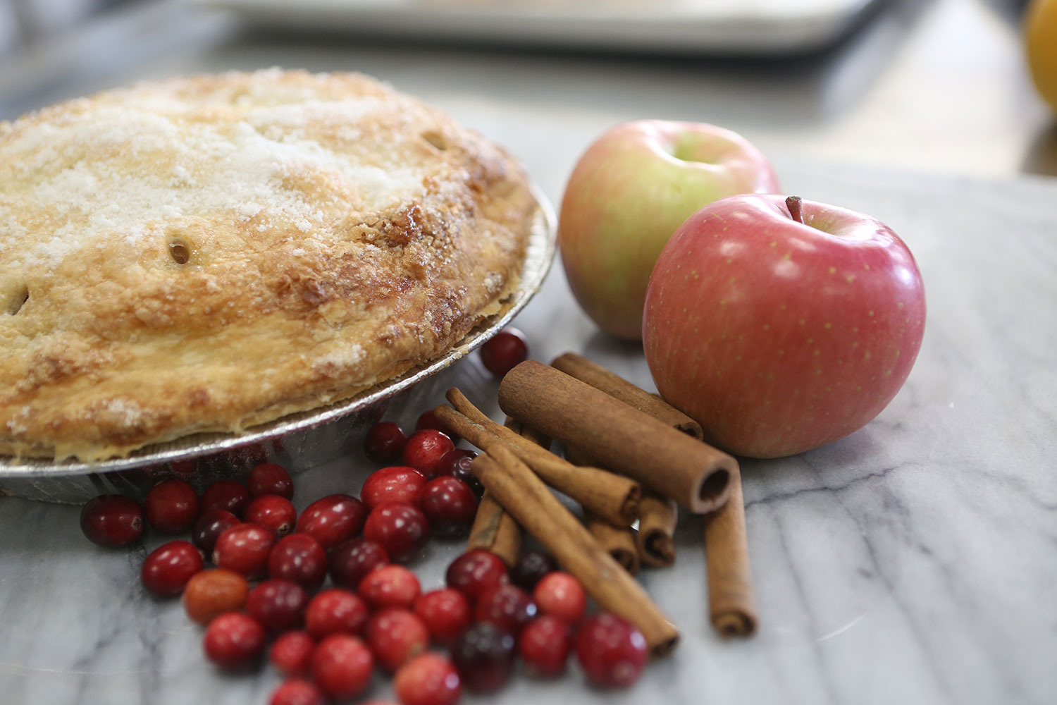 A Cranberry-apple pie with cranberries, apples, and cinnamon sticks placed to the side.