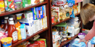 Female reaching down for items in a food pantry.