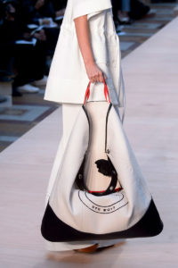 A model on the runway with an oversize white hand bag with black trim.