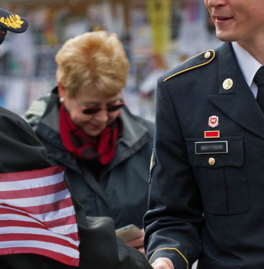 A military service member student at Buffalo State shakes hands with a veteran senior citizen soldier.