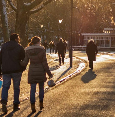 People walking a curved street in a park in winter.