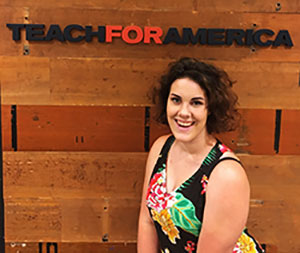Binghamton University student Miranda Currier in front of TeachForAmerica text sign.