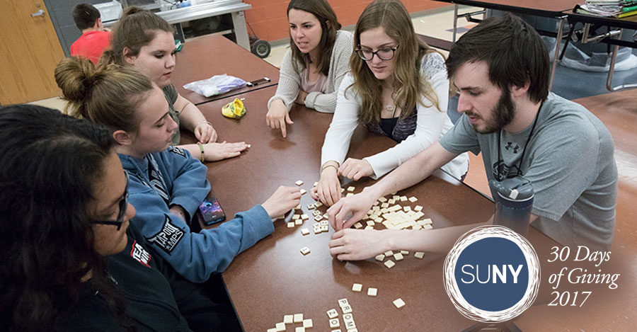 Binghamton University students play with scrabble pieces at a table.